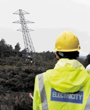 DOWN SHE GOES: A pylon is toppled before being cut up near Nethybridge. David Whittaker-Smith
