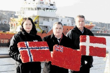 LAYING WREATHS FOR NATIONAL FLAGS: From left, Hege-Merethe Bengtsson, of the Norwegian Union of Marine Engineers, Steve Todd and ITF inspector Tore Steine, at Footdee, Aberdeen. Kevin Emslie