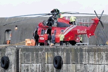 SALVAGED:  The downed helicopter is lifted off the Seven Pelican after arriving at Peterhead harbour yesterday. Kenny Elrick