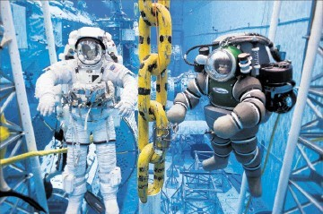 HELLO MATEY: An astronaut in his underwater-adapted spacesuit, left, takes time out of his mission training to pose with a deepsea diverin his Atomspheric Dive System (ADS) during a offshore platform testing session at NASA' Neutral Buoyancy Lab