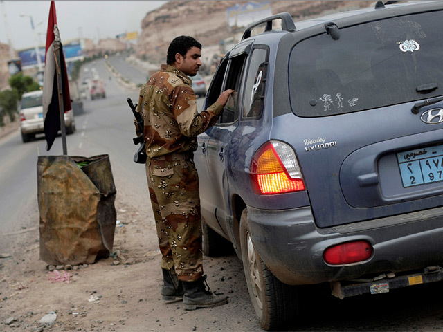 A soldier conducts inquiries at a Yemeni checkpoint. Pic: AP