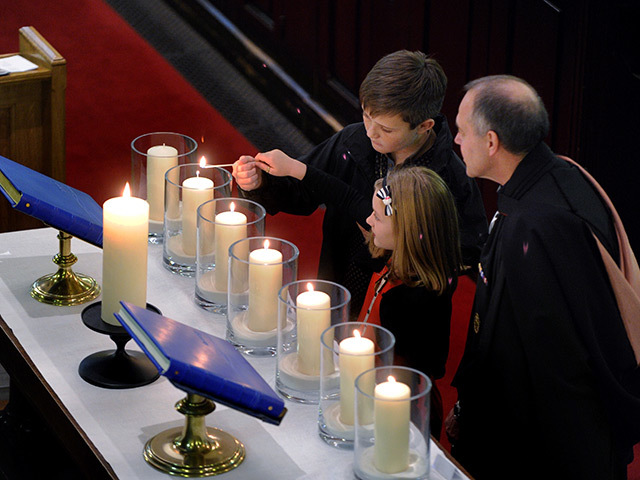 Calum and Isla Mooney light a candle in memory of their dad Eamonn Martin Mooney. Pic: Colin Rennie