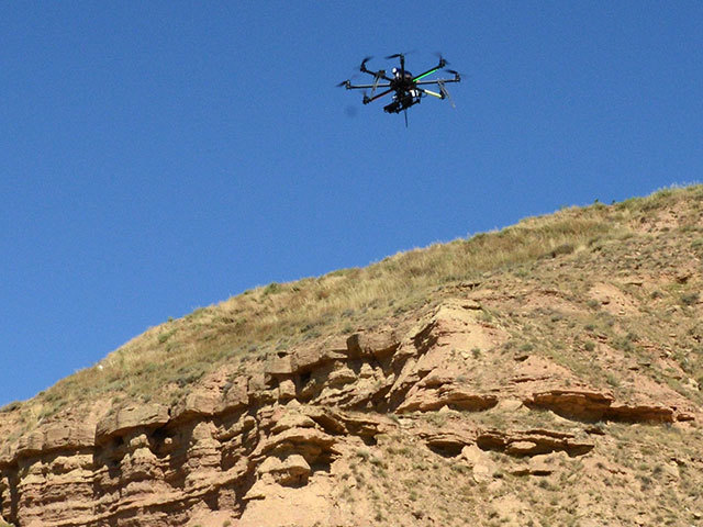 Flying robot (UAV) surveying a cliff