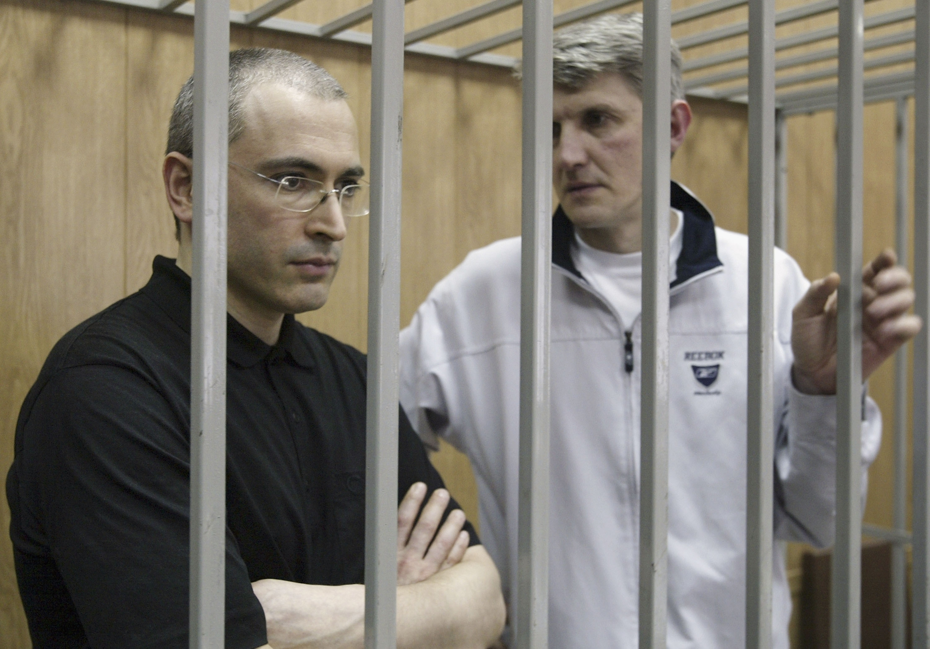 Russian oil magnate Mikhail Khodorkovsky (L) listens to close associate and fellow defendant Platon Lebedev during their trial in Moscow, July 12, 2004 in Moscow.