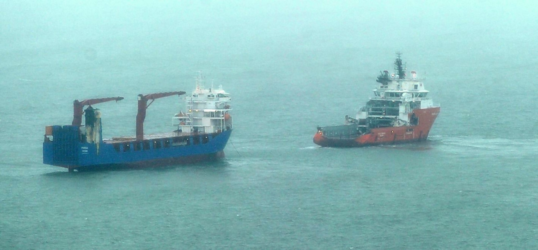 The stricken vessel  is attended by the rescue tug at the entrance to the Cromarty Firth in Easter Ross.