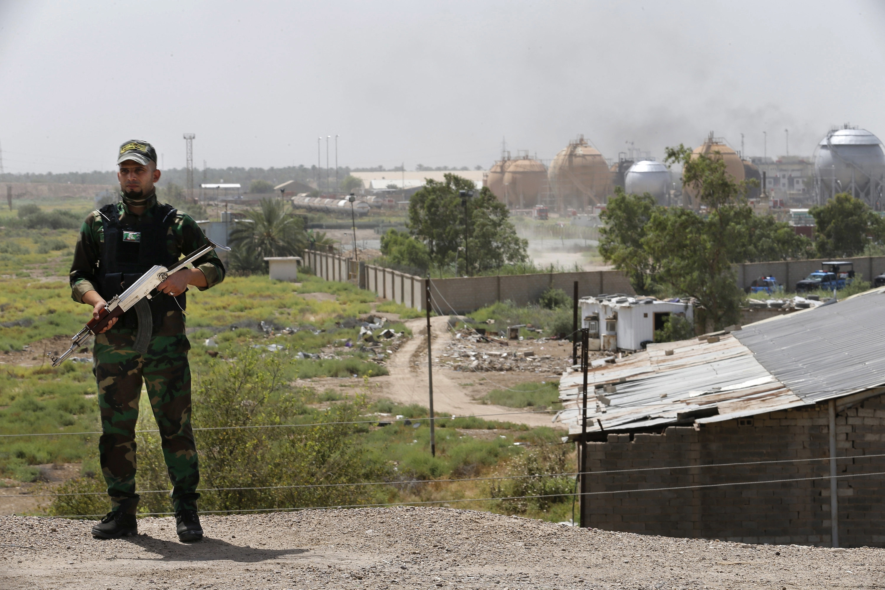 A federal police man stands guard outside the natural gas plant in Taji, 12 miles (20 kilometers) north of Baghdad, Iraq, Sunday, May 15, 2016. The Islamic State group launched a coordinated assault Sunday on a natural gas plant north of the capital that killed more than a dozen people, according to Iraqi officials.