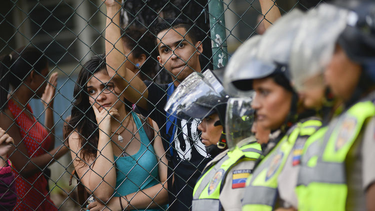 Spectators look on as Bolivarian National Police stand guard near the Central University of Venezuela during pro-opposition students marching near the Central University of Venezuela in Caracas, Venezuela, on Thursday, May 26, 2016.