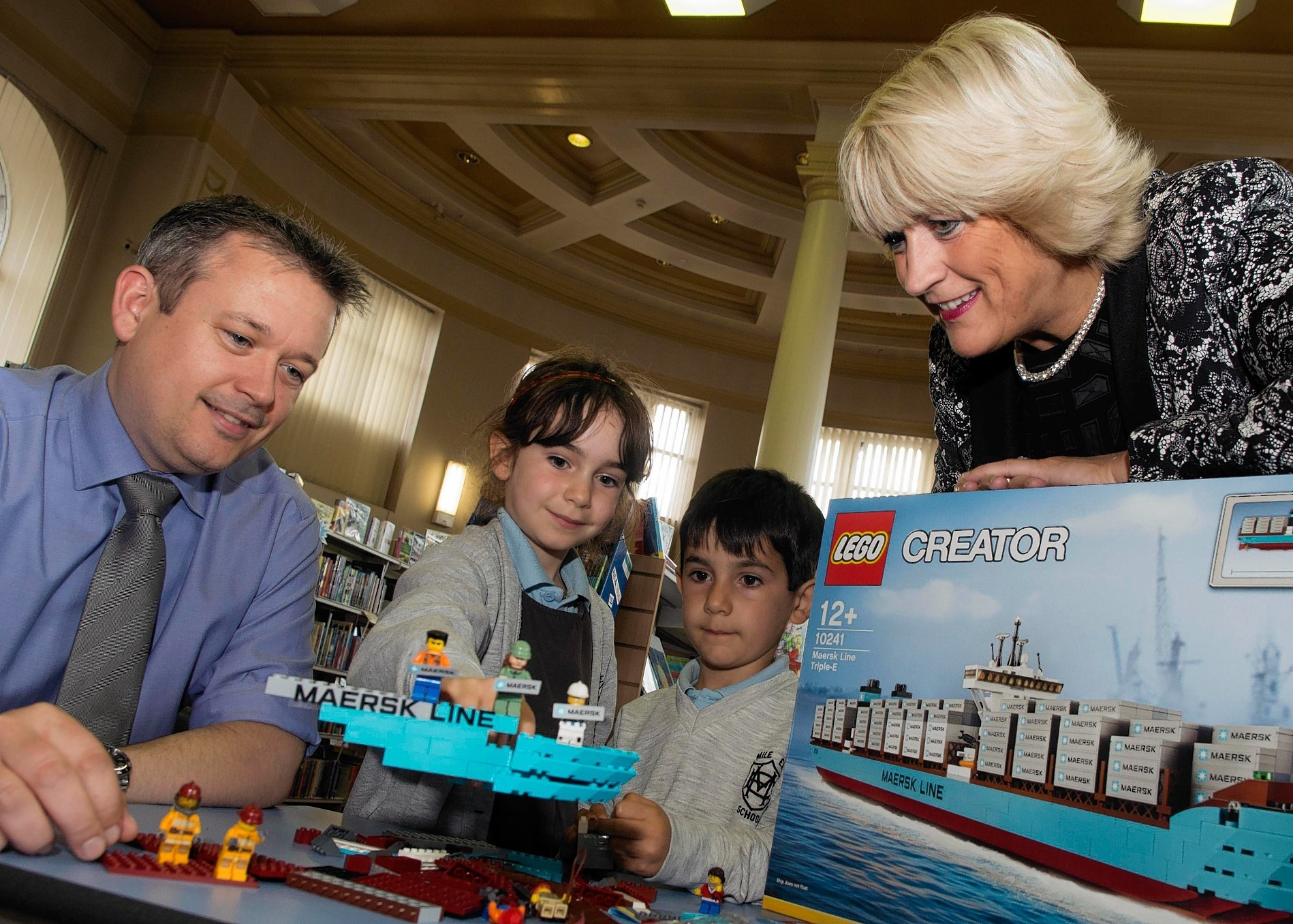 Councillor Angela taylor and Phil Masson from Maersk along with Noemi Napoletano, aged 7, and brother Alex, 6, with the new lego play kit donated by Maersk to Aberdeen City Library  Photo by Norman Adams