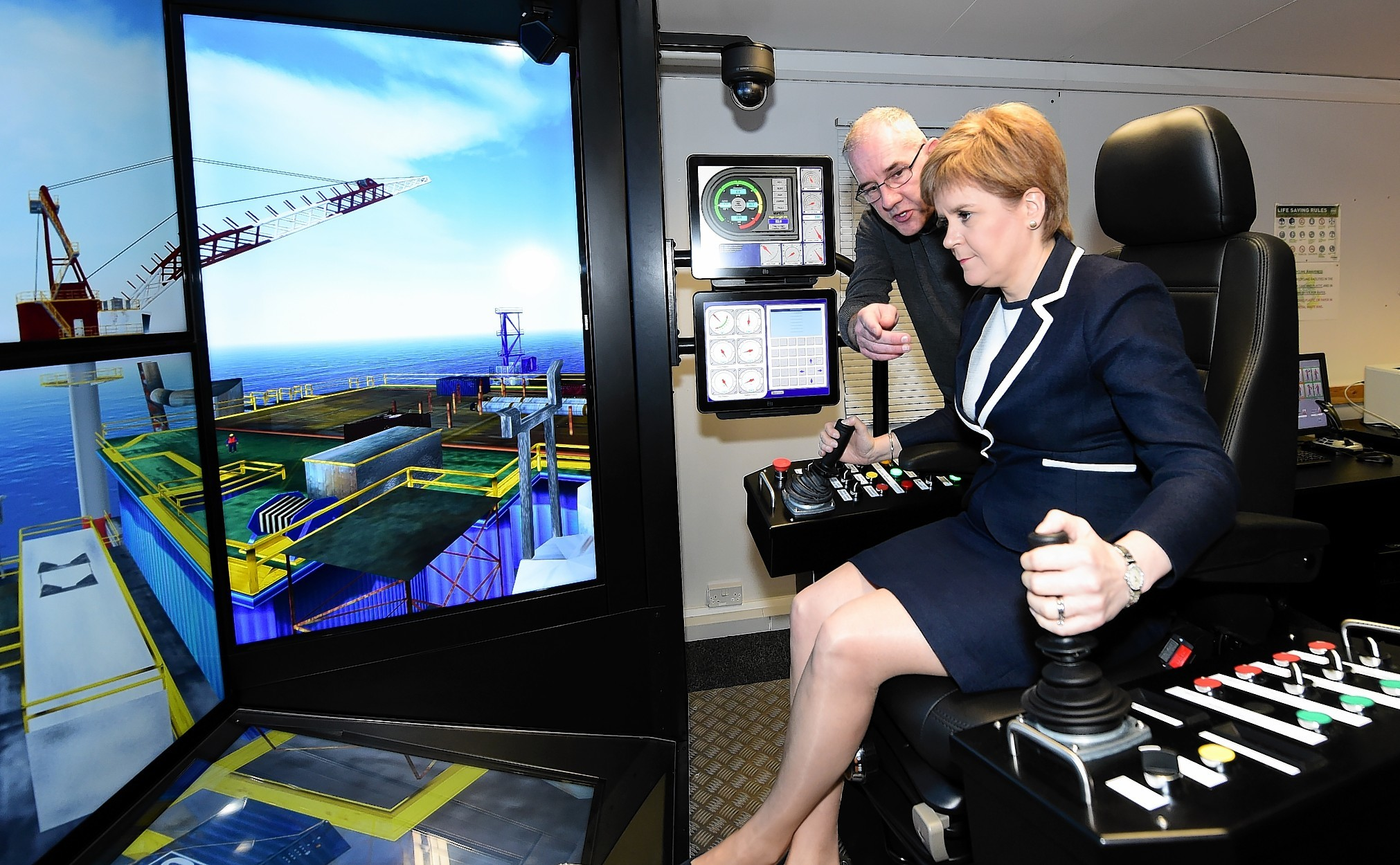 First Minister Nicola Sturgeon at on a crane simulator at Sparrows, with Trevor Dear, Training Centre Supervisor.