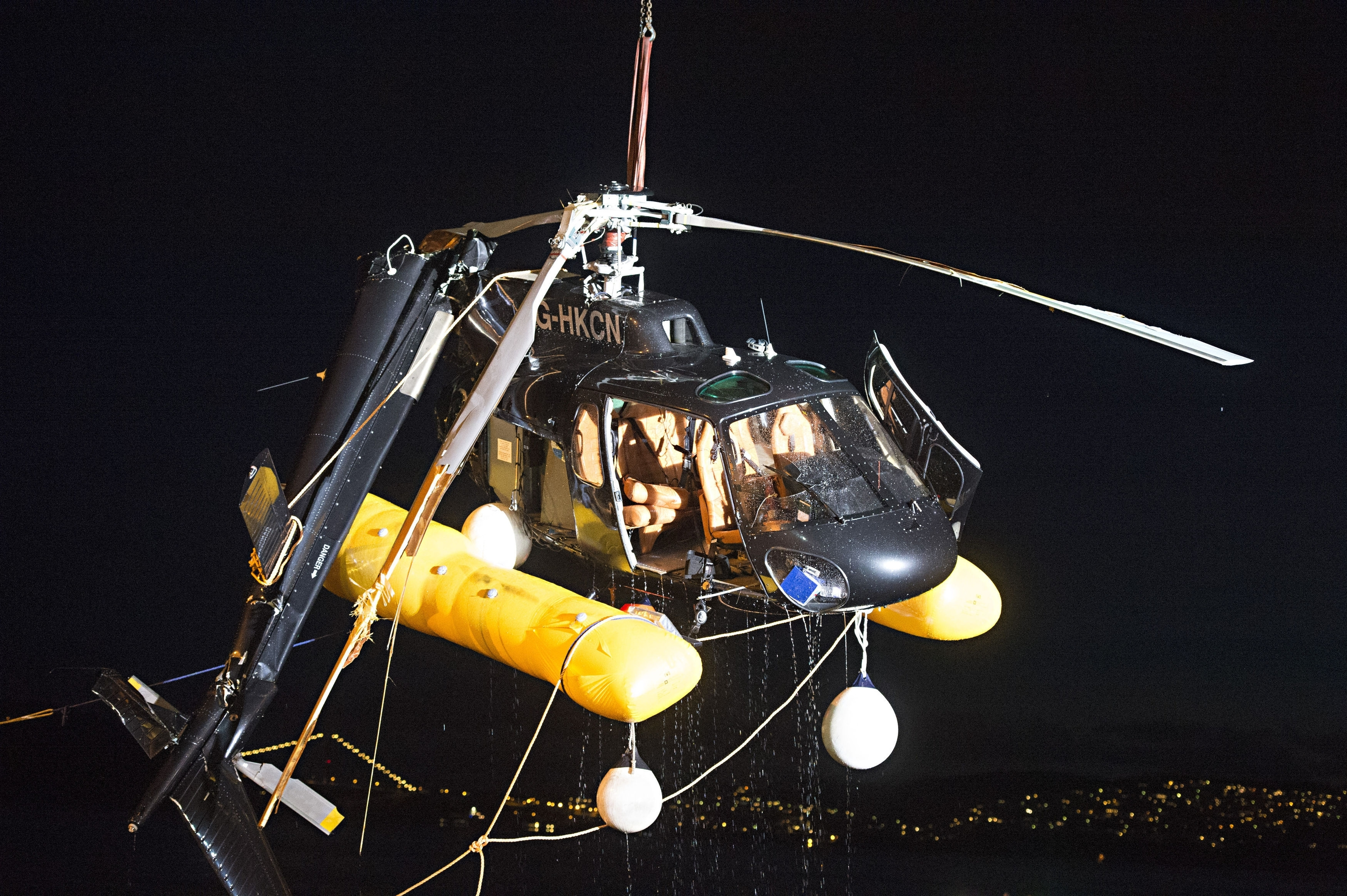A helicopter which crashed into the sea near Bergen harbour, western Norway, is seen being lifted out from the water in the early hours of Thursday May 11, 2017.
