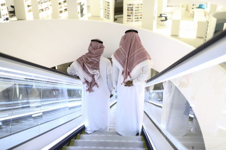 Attendees stand on an escalator as they move through the interior of the King Abdulaziz Center for World Culture during a tour of the project in Dhahran, Saudi Arabia, on Friday, Nov. 25, 2016. When completed, the project designed for the Saudi Arabian Oil Co. (Aramco) will contain diverse cultural facilities, including an auditorium, cinema, library, exhibition hall, museum and archive.
