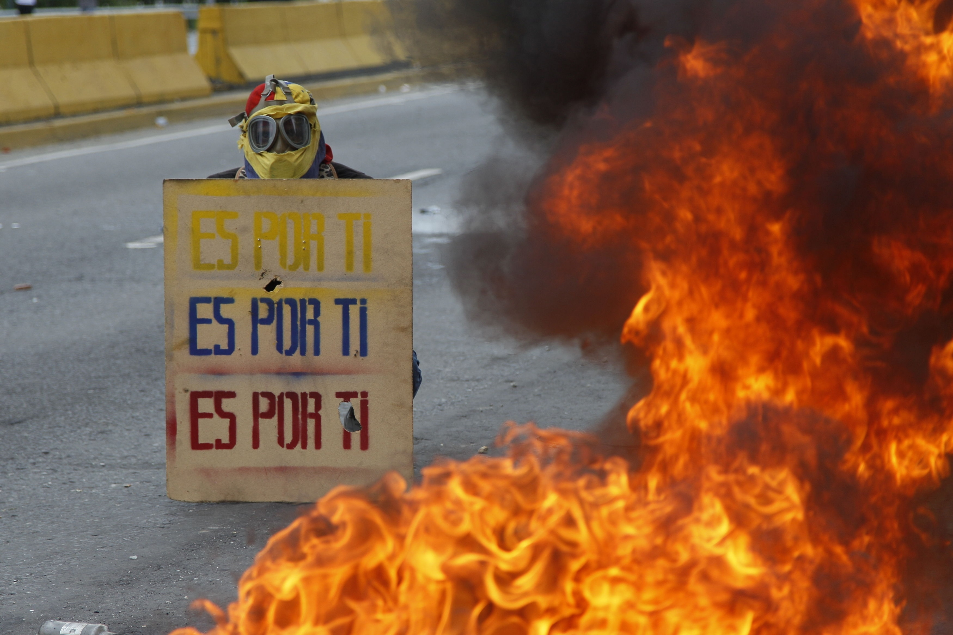 "A demonstrator holds a sign that doubles a shield that reads in Spanish ""It's for you,"" during a national sit-in against President Nicolas Maduro, in Caracas, Venezuela, Monday, May 15, 2017."