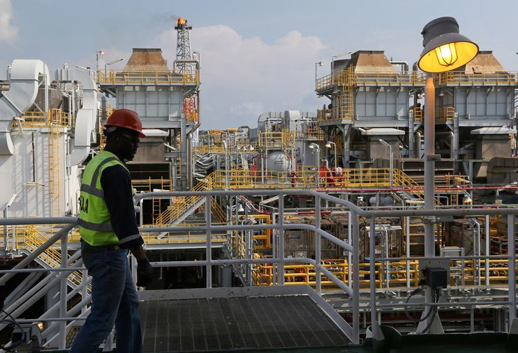 An employee walks along an upper level walkway aboard the Agbami floating oil production, storage and offloading vessel (FPSO), operated by Chevron Corp., in the Agbami deepwater oilfield in the Niger Delta, Nigeria. Photographer: George Osodi/Bloomberg