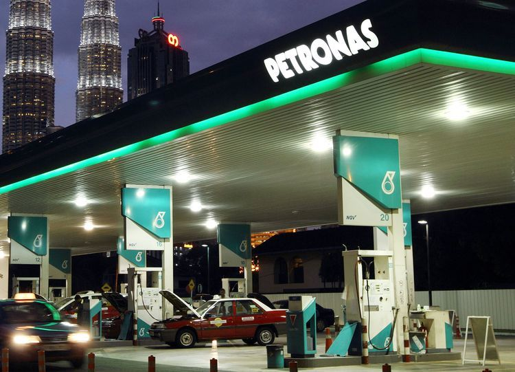 A Petroliam Nasional Bhd. (Petronas) gas station stands in front of the Petronas Twin Towers (KLCC), background center, at night in Kuala Lumpur, Malaysia. Photographer: Goh Seng Chong/Bloomberg