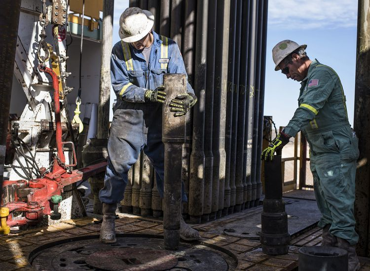 Precision Drilling oil rig operators install a bit guide on the floor of a Royal Dutch Shell Plc oil rig near Mentone, Texas, U.S.