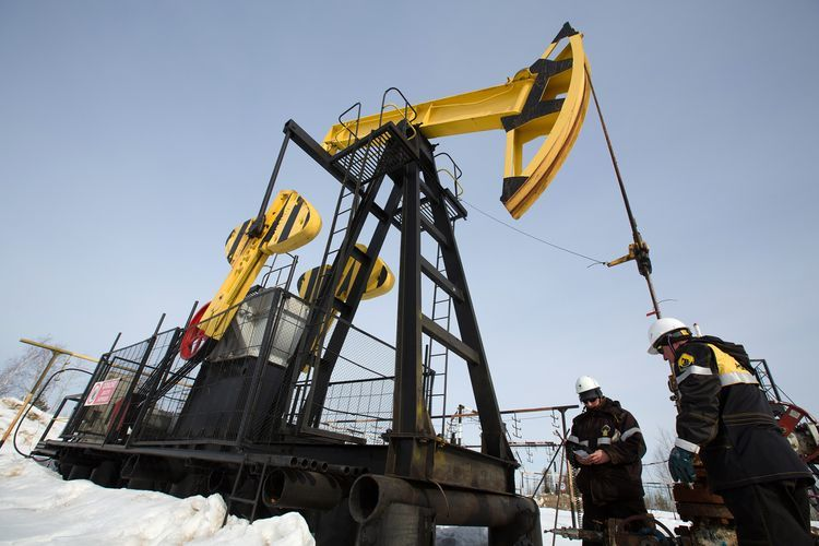 Workers inspect an oil pumping jack, also known as a 'nodding donkey' at a pumping site, operated by Rosneft PJSC, in the Samotlor oilfield near Nizhnevartovsk, Russia, on Wednesday, March 22, 2017. Photographer: Andrey Rudakov/Bloomberg