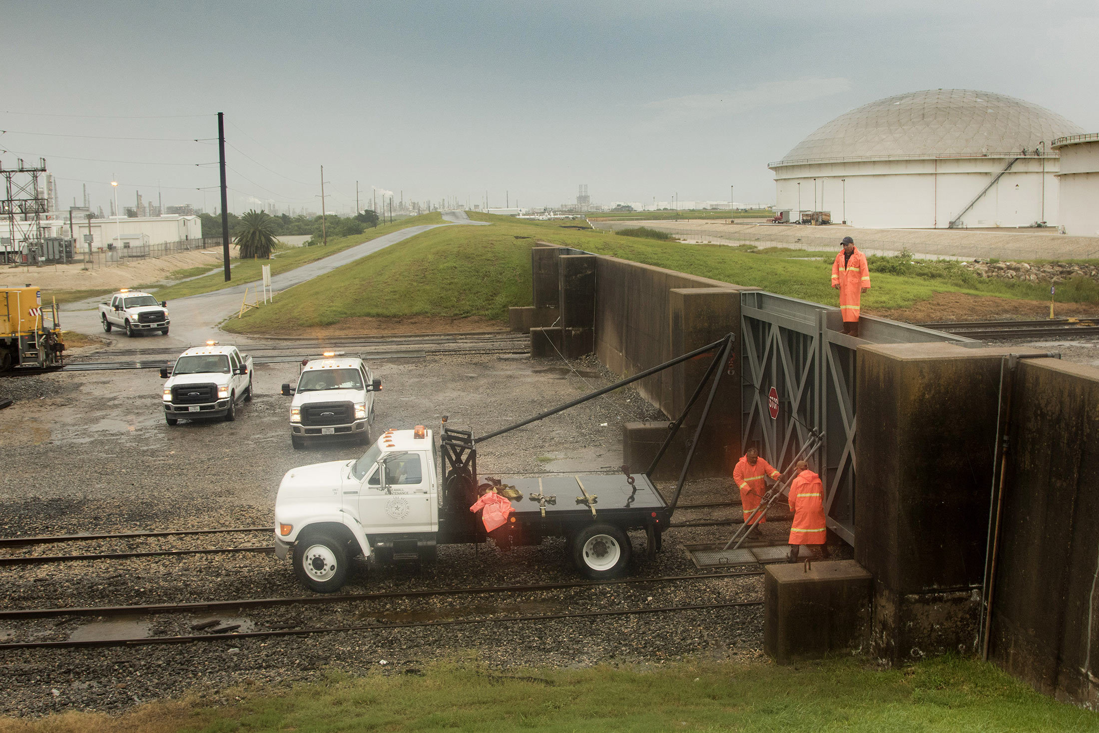 Workers secure a flood gate along the railroad tracks entering the Enterprise Products Partners LP marine terminal ahead of Hurricane Harvey in Texas City, Texas, U.S., on Friday, Aug. 25, 2017. Hurricane Harveystrengthened as it headed toward landfall in Texas, forecast to become the worst storm to strike the region in more than a decade. The price of gasolineralliedas it threatened to wreak havoc on the heart of America's energy sector. Photographer: F. Carter Smith/Bloomberg via Getty Images