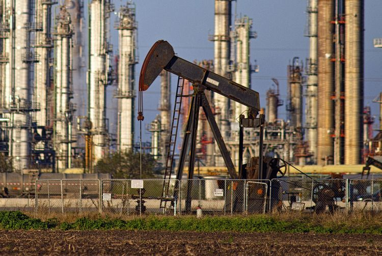 A refinery stands in the background as a pump jack operates in an oil field near Corpus Christi, Texas, U.S., on Thursday, Jan. 7, 2016. Crude oil slid Thursday to the lowest level since December 2003 as turbulence in China, the worlds biggest energy consumer, prompted concerns about the strength of demand. Photographer: Eddie Seal/Bloomberg
