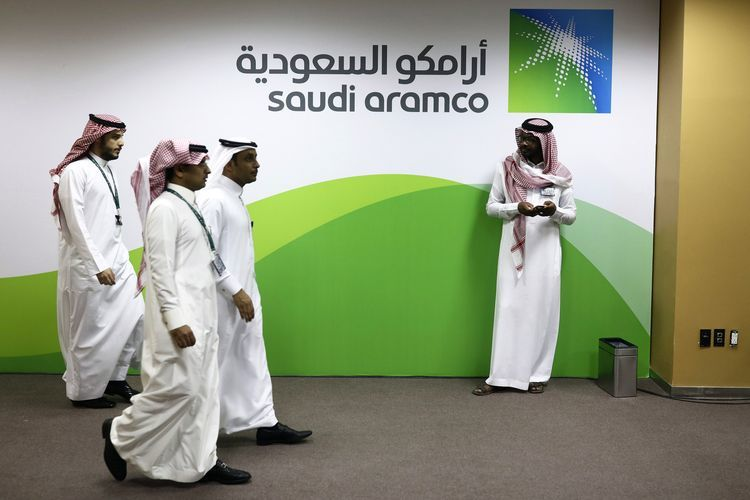 Attendees walk by a sign for the Saudi Arabian Oil Co. (Aramco) on display inside the King Abdulaziz Center for World Culture during a tour of the project in Dhahran, Saudi Arabia, on Friday, Nov. 25, 2016. When completed, the project designed for the Saudi Arabian Oil Co. (Aramco) will contain diverse cultural facilities, including an auditorium, cinema, library, exhibition hall, museum and archive. Photographer: Simon Dawson/Bloomberg