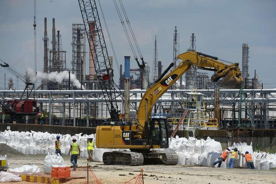 Workers build a wall of sandbags along the damaged levee near the Valero Port Arthur refinery in preparation for Hurricane Harvey on Thursday. Photo taken Thursday 8/24/17 Ryan Pelham/The Enterprise