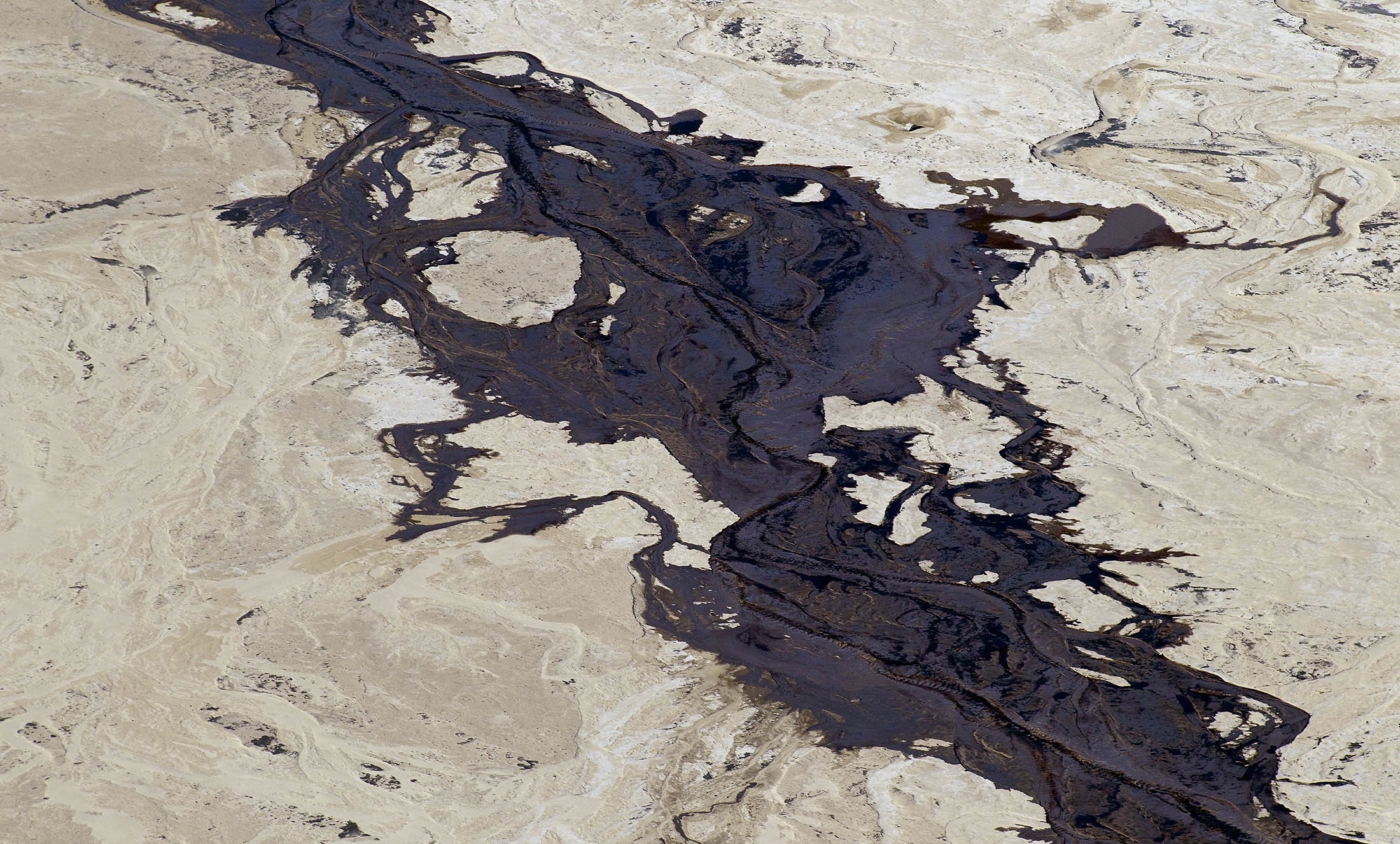 The Syncrude Canada Ltd. tailings pond stands in the Athabasca oil sands in this aerial photograph taken near Fort McMurray, Alberta, Canada. Photographer: Ben Nelms/Bloomberg