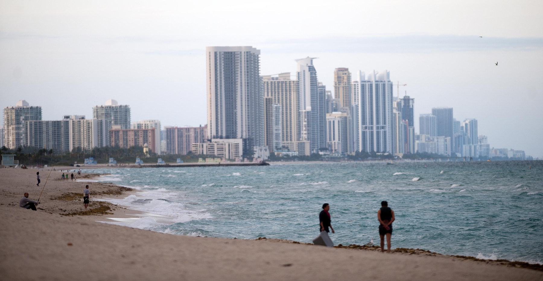 People stand on the shore in front of the skyline of Miami Beach, Florida, U.S., on Wednesday, Feb. 20, 2013. Photographer: Ty Wright/Bloomberg