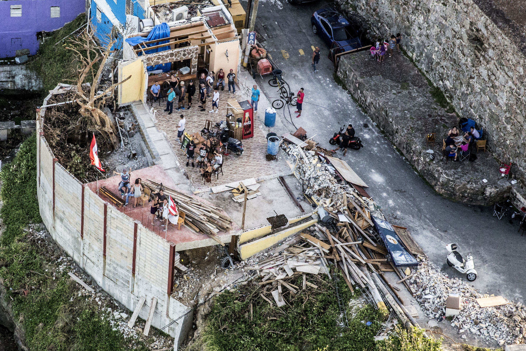People stand in a bar damaged from Hurricane Maria in this aerial photograph taken above La Perla, San Juan, Puerto Rico, on Monday, Sept. 25, 2017. Photographer: Alex Wroblewski/Bloomberg