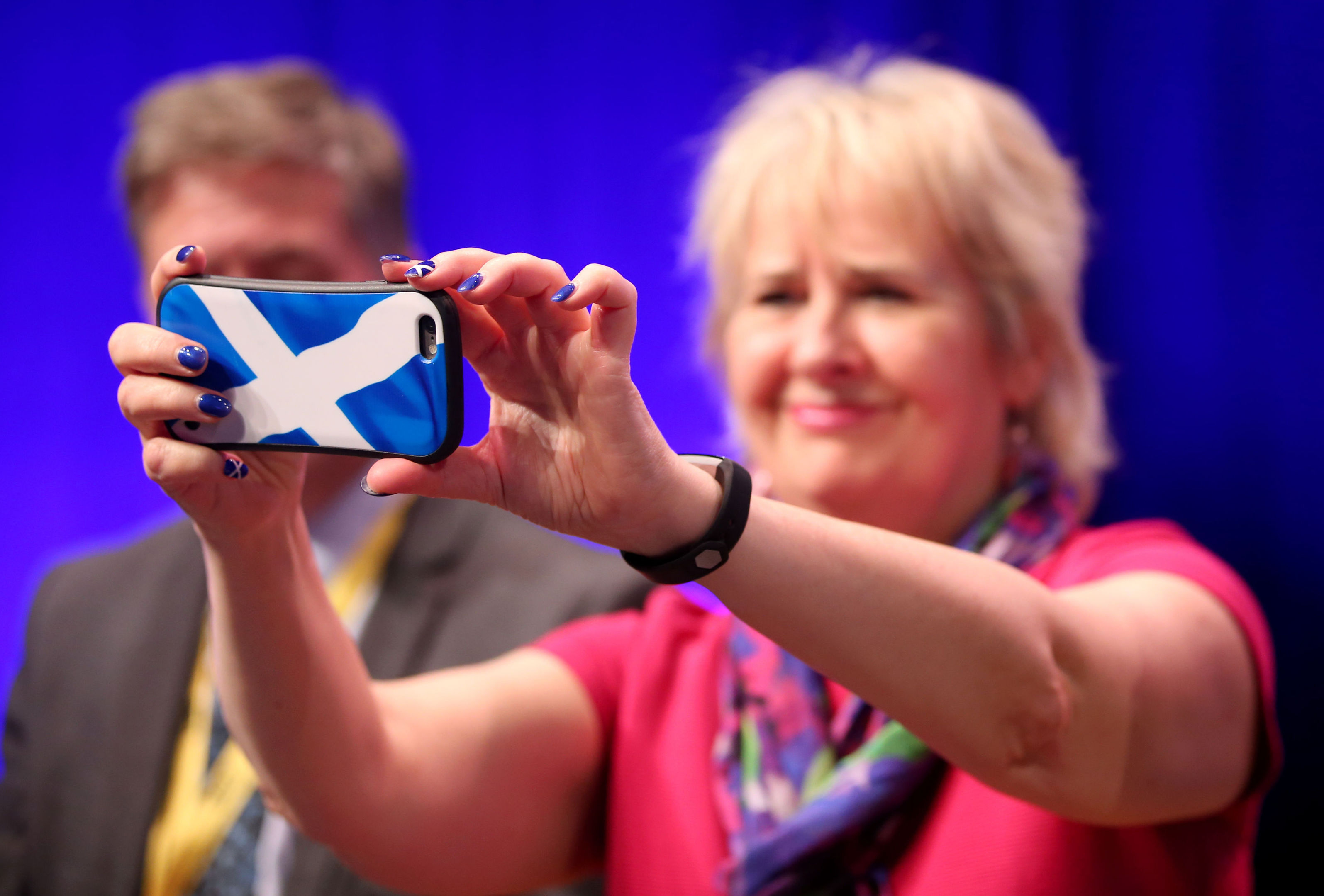 Roseanna Cunningham takes pictures on her phone as First Minister Nicola Sturgeon delivers her keynote speech at the Scottish National Party conference at the SEC Centre in Glasgow.