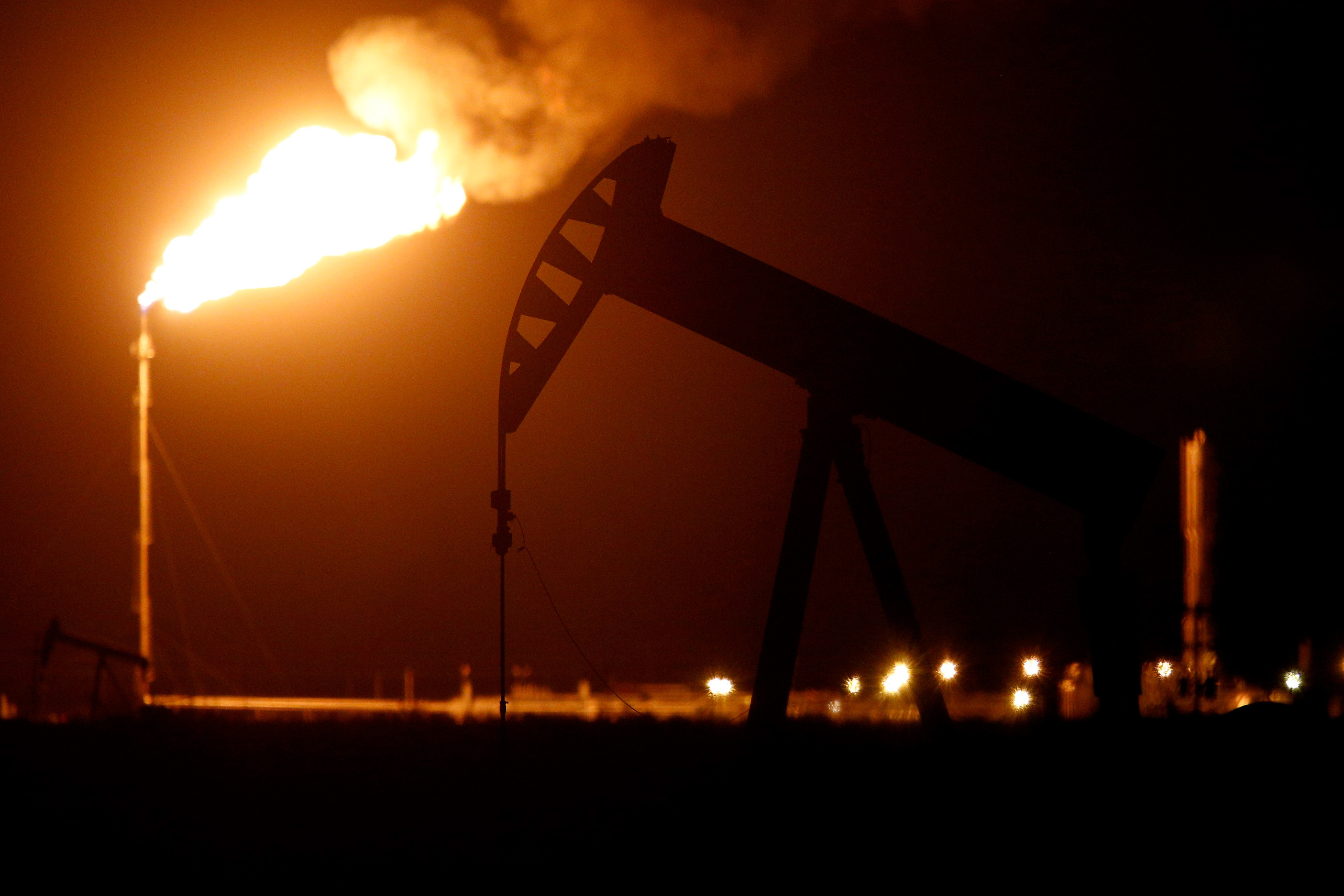 The silhouette of an electric oil pump jack is seen near a flare at night in the oil fields surrounding Midland, Texas