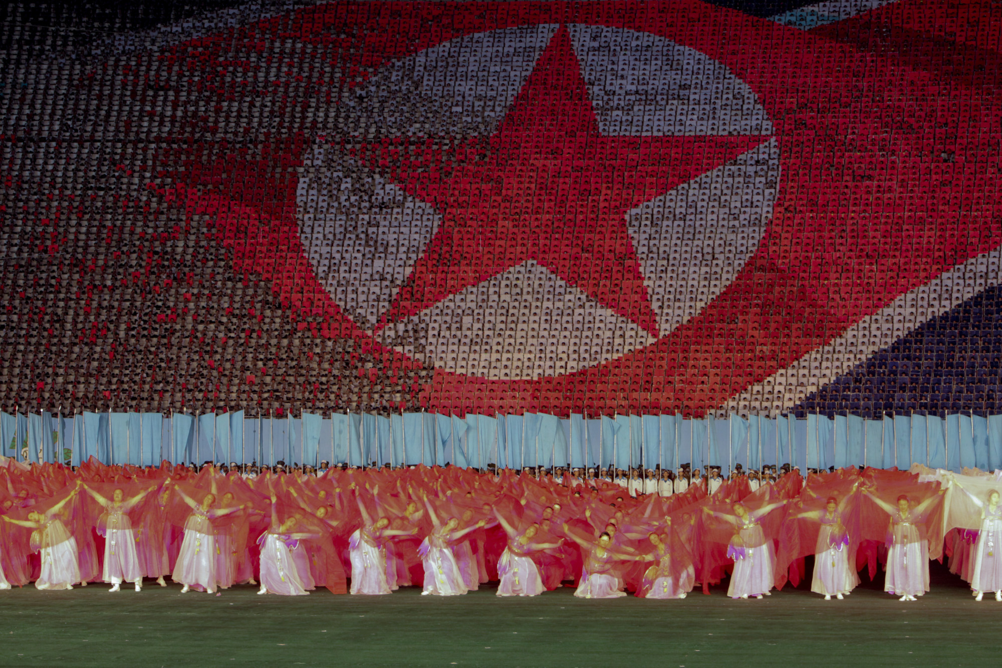 Performers dance in front of a depiction of the North Korean flag in Rungrado May Day Stadium during a ceremony commemorating the 65th anniversary of the Korea Worker's Party in Pyongyang, North Korea. Photographer: Bloomberg/Bloomberg