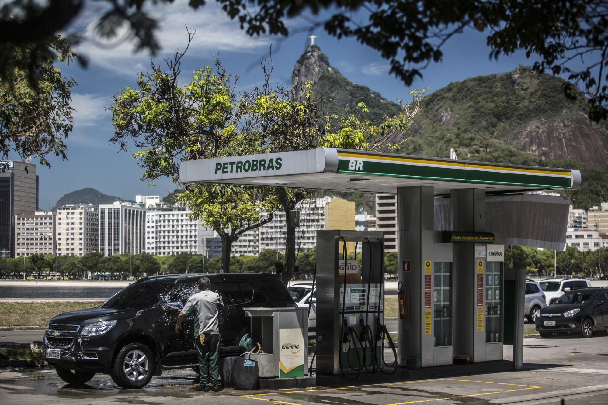 An attendant washes a car at a Petroleo Brasileiro SA (Petrobras) gas station in Rio de Janeiro, Brazil, on Friday, Nov. 10, 2017. Petroleo Brasileiro SA is scheduled to release earnings figures on November 13. Photographer: Dado Galdieri/Bloomberg