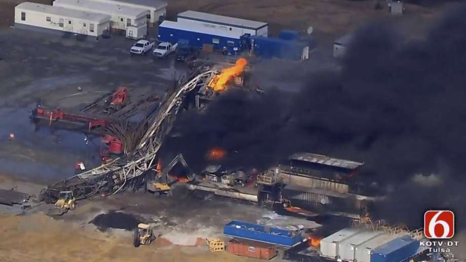 In this photo provided from a frame grab from Tulsa's KOTV/NewsOn6.com, fires burn at an eastern Oklahoma drilling rig near Quinton, Okla., Monday Jan. 22, 2018. Five people are missing after a fiery explosion ripped through a drilling rig, sending plumes of black smoke into the air and leaving a derrick crumpled on the ground, emergency officials said. (Christina Goodvoice, KOTV/NewsOn6.com via AP