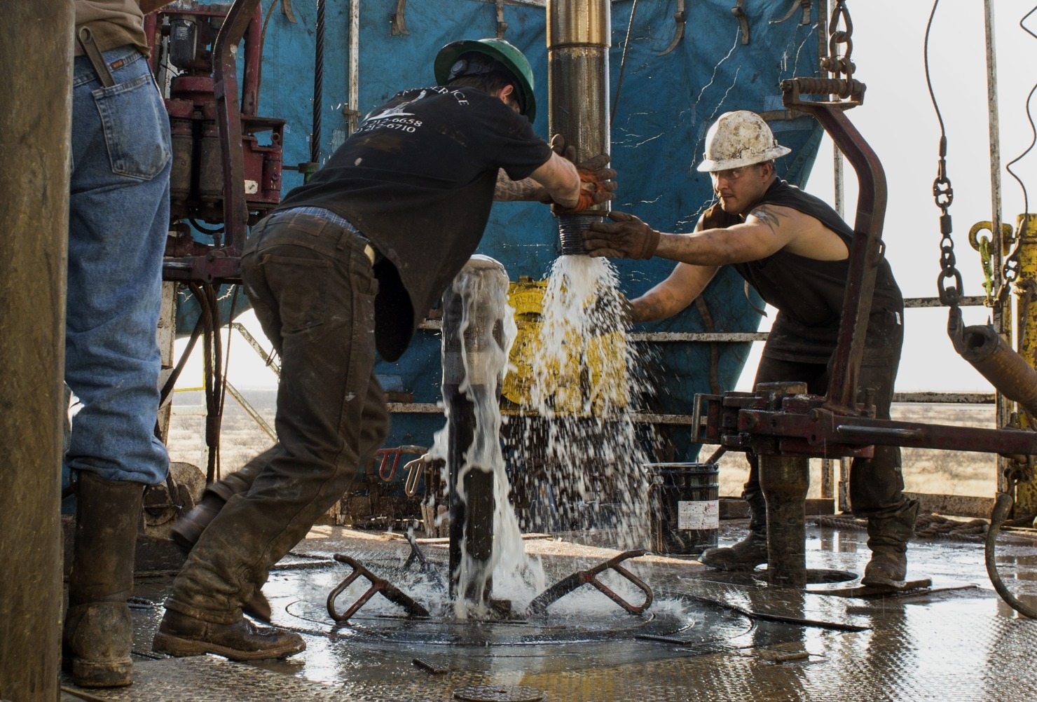 Workers connect drill bits and drill collars, used to extract natural petroleum, on Endeavor Energy Resources LP's Big Dog Drilling Rig 22 in the Permian basin outside of Midland, Texas, U.S., on Friday, Dec. 12, 2014.  Photographer: Brittany Sowacke/Bloomberg