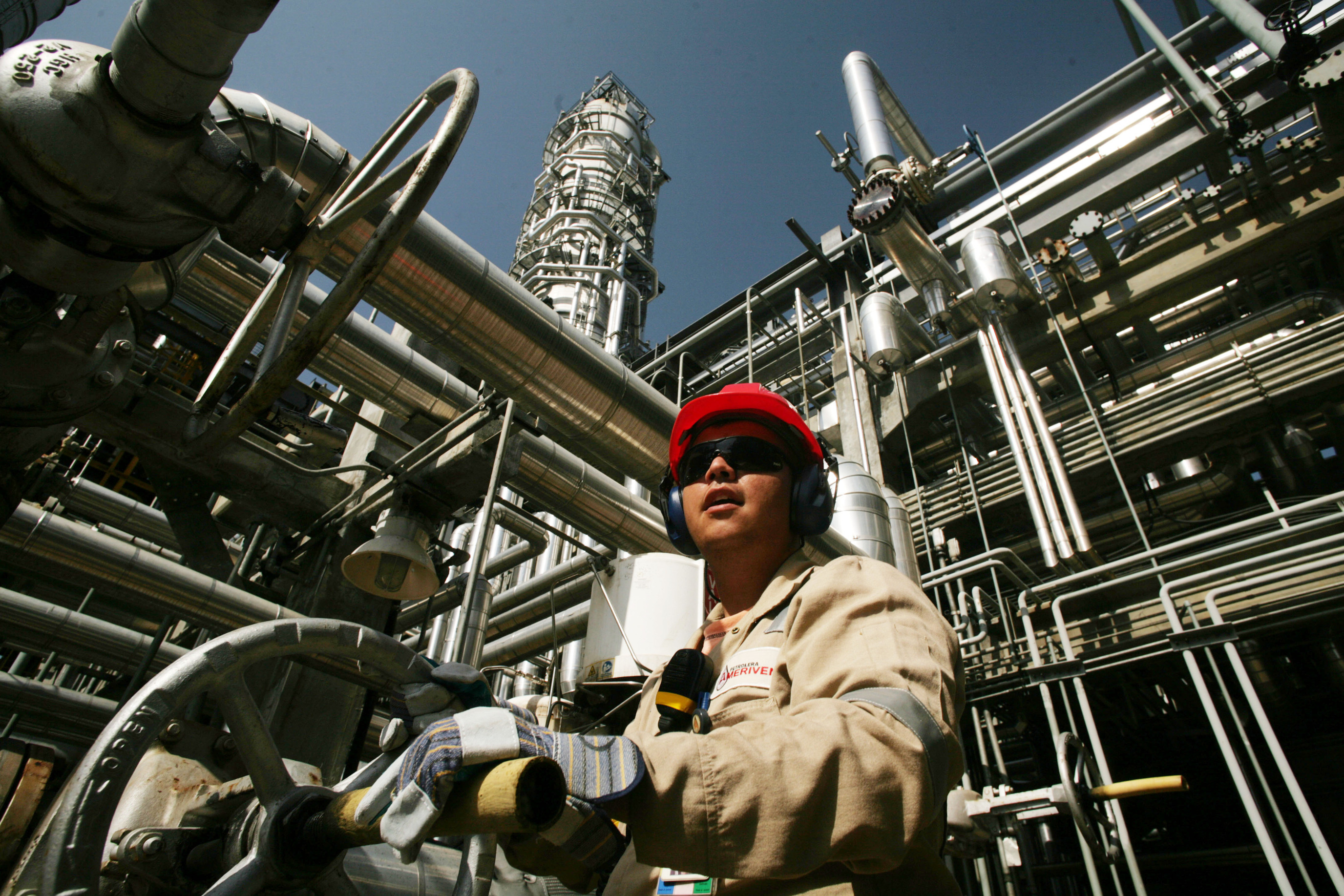 A worker opens a valve at the Ameriven oil refinery, one of the four companies at the Jose Complex in Anzoategui state, 200 miles East from Caracas, Venezuela, on Thursday, Sept. 13, 2007.  Photographer: DIEGO GIUDICE/Bloomberg