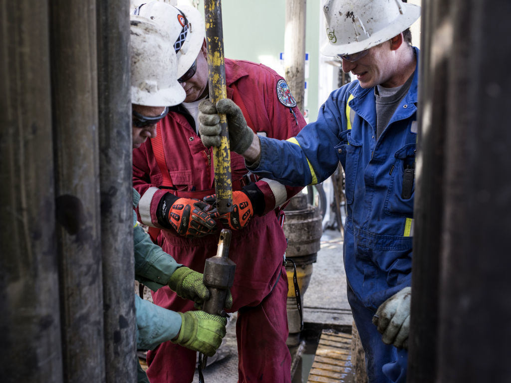 Precision Drilling oil rig operators install a bit guide on the floor of a Royal Dutch Shell Plc oil rig near Mentone, Texas, U.S., on Thursday, March 2, 2017. Exxon Mobil Corp., Royal Dutch Shell and Chevron Corp., are jumping into American shale with gusto, planning to spend a combined $10 billion this year, up from next to nothing only a few years ago. Photographer: Bloomberg/Bloomberg