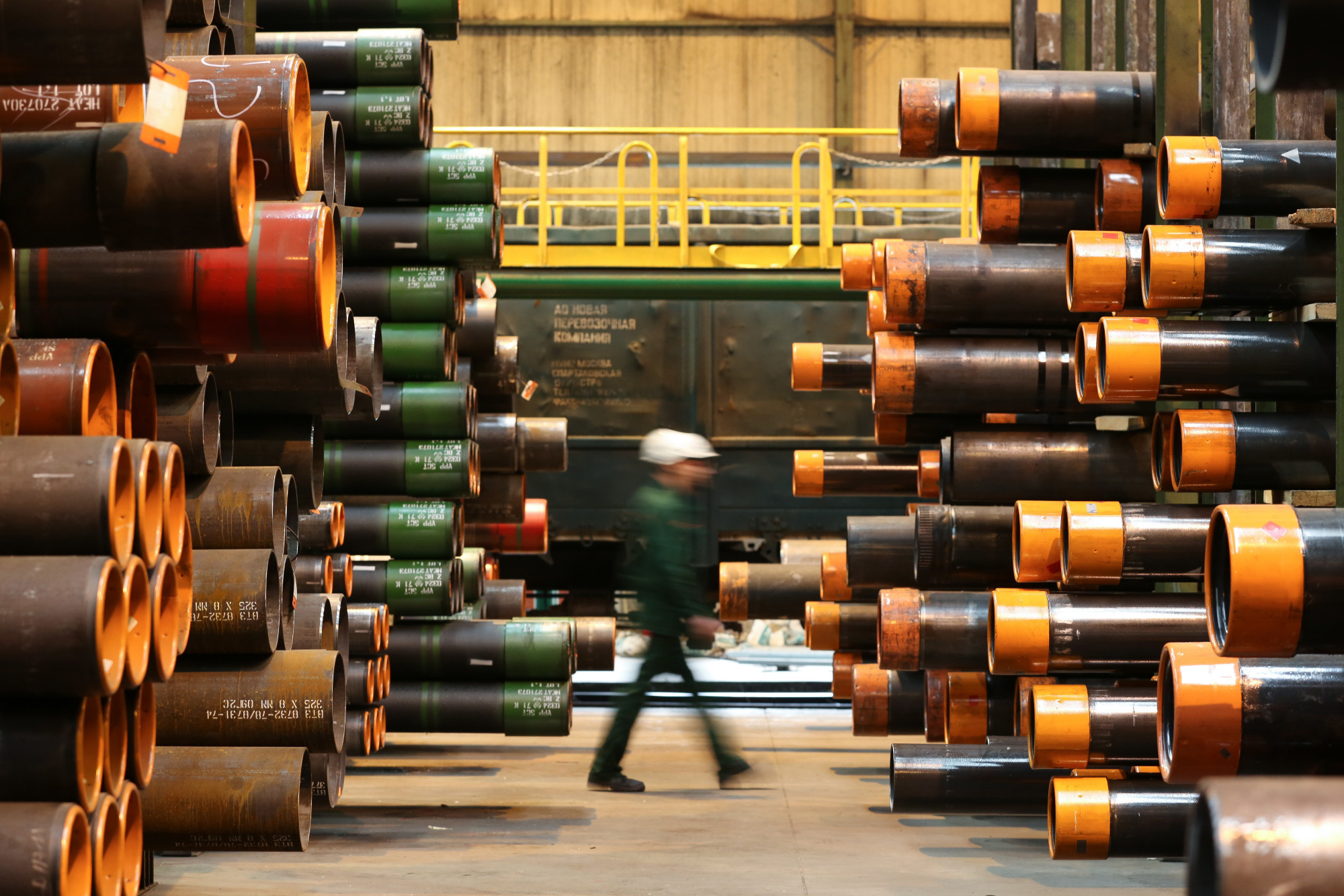 A worker passes stores of seamless steel pipes for use in oil and gas pipelines in a storage area at the Volzhsky Pipe Plant OJSC, operated by TMK PJSC, in Volzhsky, Russia, on March 30, 2017.  Photographer: Andrey Rudakov/Bloomberg