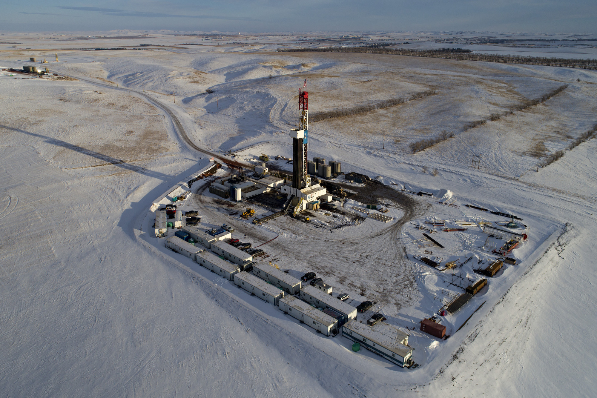 A Unit Drilling Co. rig stands in the Bakken Formation in this aerial photograph outside Watford City, North Dakota, U.S., on Friday, March 9, 2018. When oil sold for $100 a barrel, many oil towns dotting the nation's shale basins grew faster than its infrastructure and services could handle. Since 2015, as oil prices floundered, Williston has added new roads, including a truck route around the city, two new fire stations, expanded the landfill, opened a new waste water treatment plant and started work on an airport relocation and expansion project. Photographer: Daniel Acker/Bloomberg