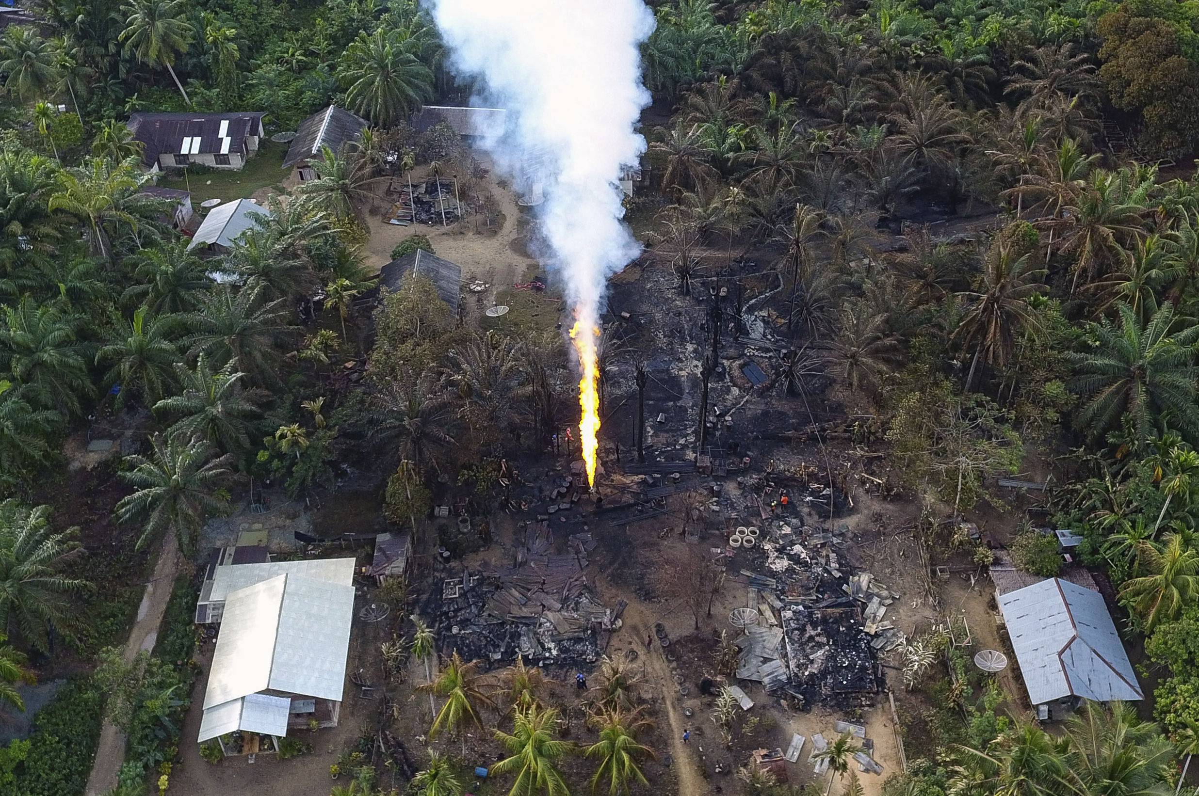 This aerial photo shows ruins of houses around a burning oil well that exploded after it caught fire early Wednesday, in Pasir Putih, easter Aceh, Indonesia, Thursday, April 26, 2018. The newly drilled, unregulated oil well in western Indonesia exploded into flames on Wednesday, burning to death a number of people and injuring dozens of others. (AP Photo/Zik Maulana)