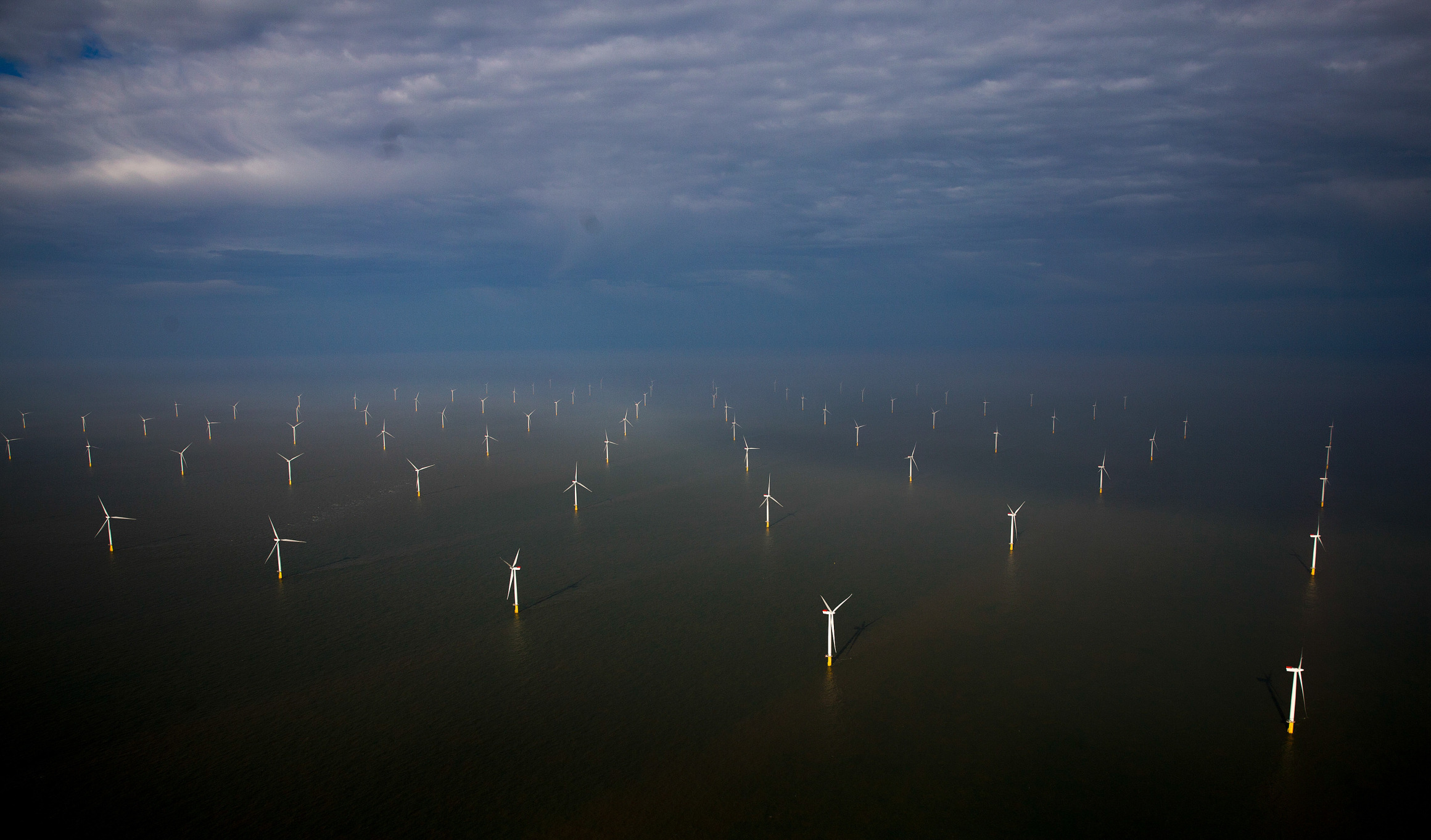 Wind turbines sit in the North Sea at the London Array offshore wind farm, a partnership between Dong Energy A/S, E.ON AG and Abu Dhabi-based Masdar, in the Thames Estuary, U.K. Photographer: Simon Dawson/Bloomberg