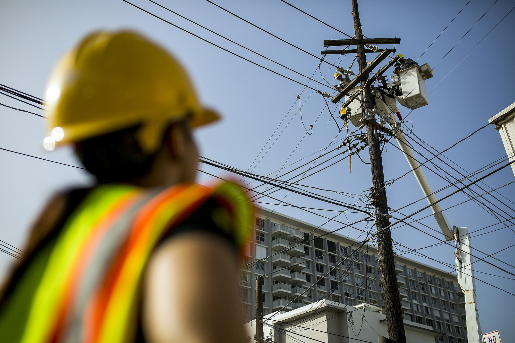 Puerto Rico Electric Power Authority (PREPA) employees fix power lines in Santurce, San Juan, Puerto Rico, on Thursday, Oct. 19, 2017. For longer than most can remember, Puerto Ricans have paid some of the highest energy costs in the U.S. to a notoriously unreliable utility that neglected their grid for years and runs fossil-fuel plants that may be damaging their lungs. A month after Hurricane Maria devastated the island, power lines still lay slack along roads, utility poles are snapped clean in half, and most Puerto Ricans remain in the dark. Photographer: Xavier Garcia/Bloomberg