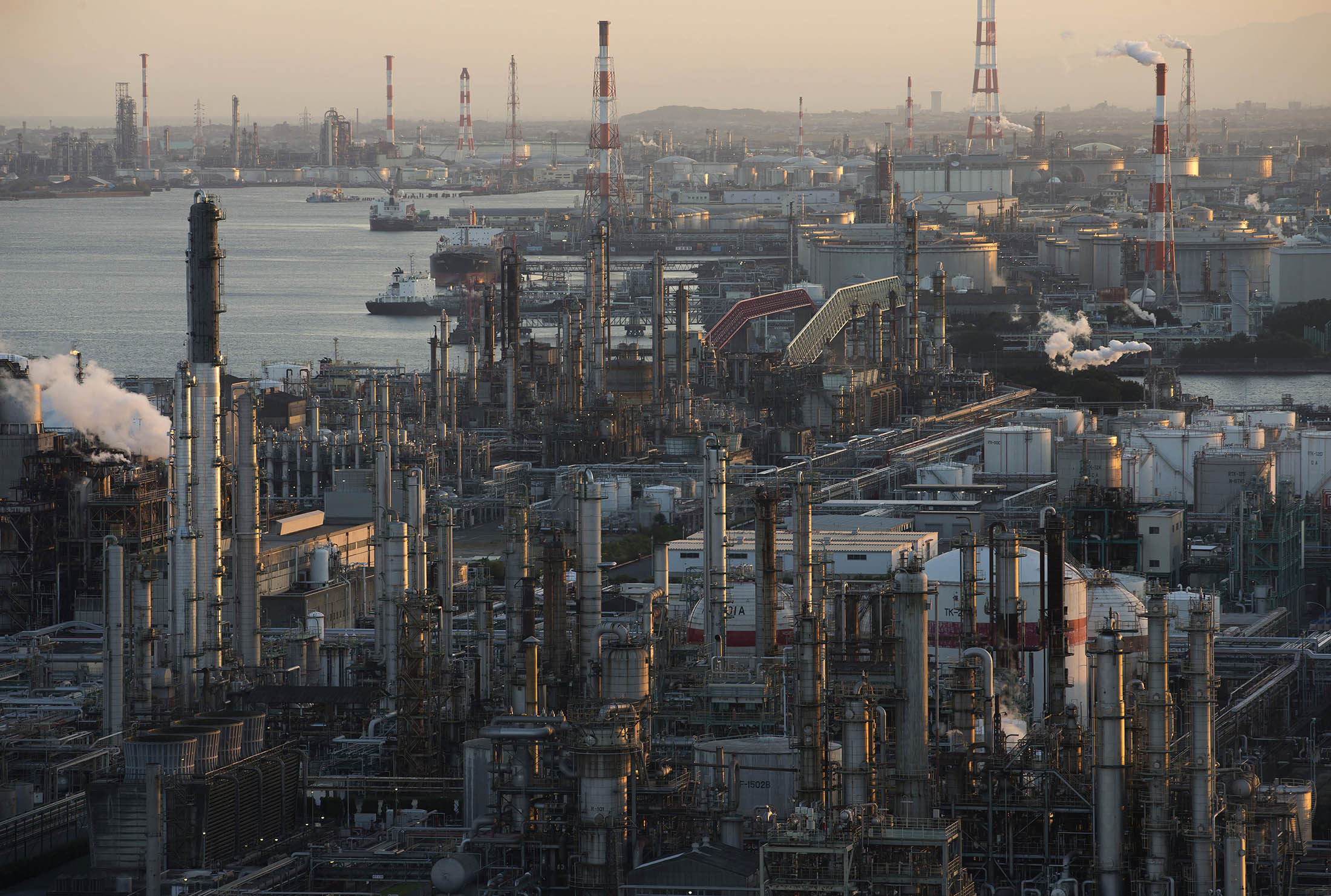 Chemical plants and oil refineries stand at the Yokkaichi industrial complex at dusk in Yokkaichi, Mie Prefecture, Japan, on Friday, Oct. 27, 2016. The Paris Agreement, the most sweeping climate change agreement to combat global warming to date, will enter into force Nov. 4. Photographer: Tomohiro Ohsumi/Bloomberg