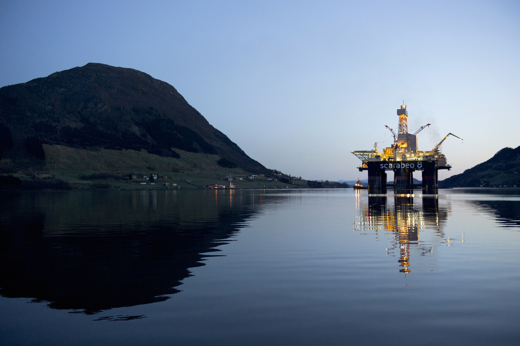 The Scarabeo 8 deepwater oil drilling rig, operated by ENI Norge AS, stands illuminated at night after being re-fitted at the Westcon AS yard in Olensvag, Norway, on Tuesday, April 3, 2012.  Photographer: Kristian Helgesen/Bloomberg