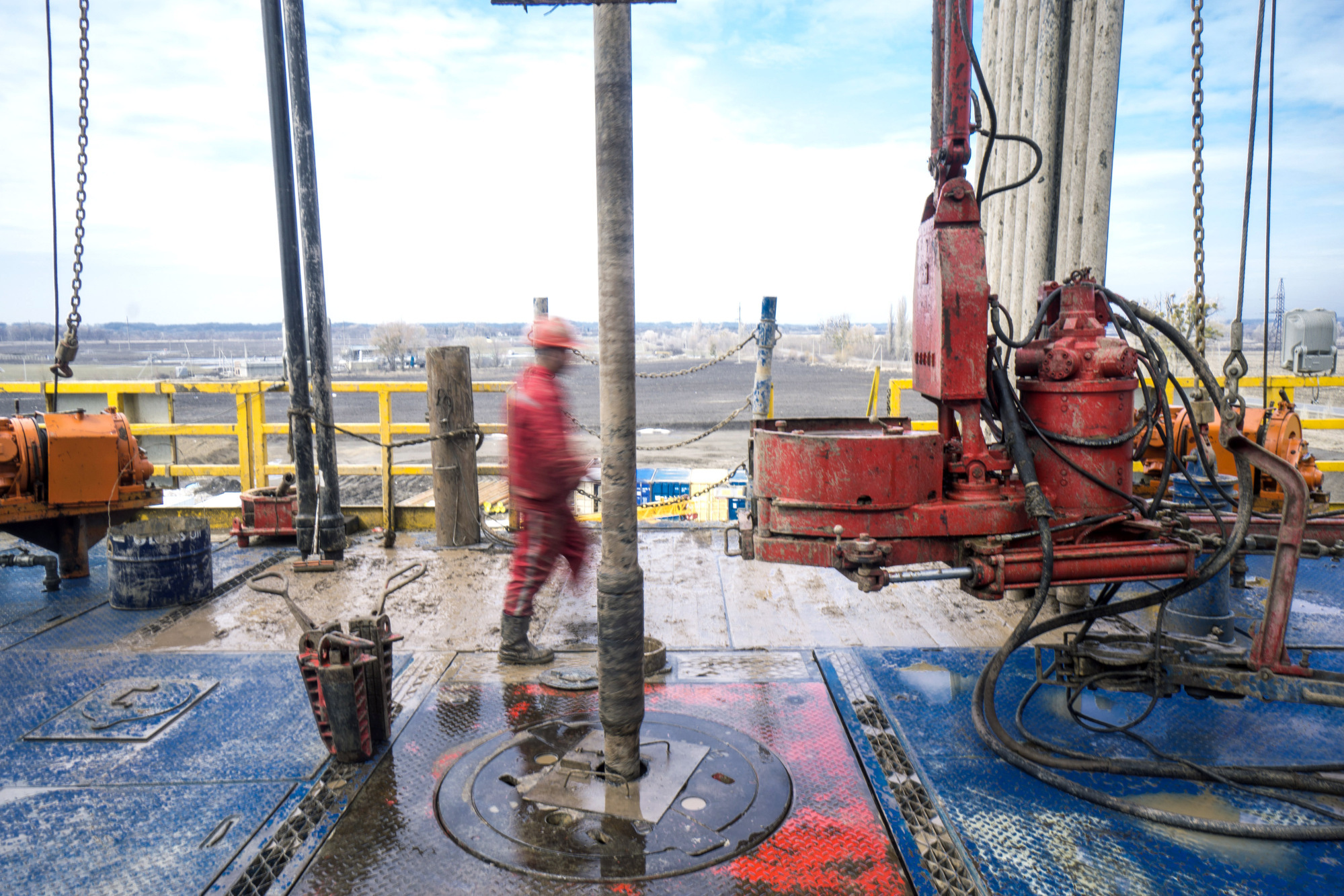 A Chinese worker from XinJiang Beiken Energy Engineering Stock Co. Ltd. walks past the turntable and drill pipe during gas drilling operations for the Ukrgazvydobuvannya Subsidiary Co. of Naftogaz of Ukraine National JSC in Poltava region, Ukraine, on Wednesday, April 4, 2018. Ukraine transports about one third of Russia's natural gas supplies to the European Union through a pipeline network connected with Slovakia, Romania, Hungary, Poland and Moldova. Photographer: Vincent Mundy/Bloomberg
