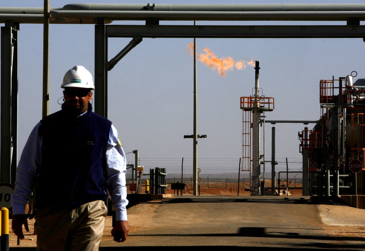 ALGERIA - DECEMBER 14: An employee walks in front of a gas flare at the In Salah Gas (ISG) Krechba Project, run by Sonatrach, British Petroleum (BP), and StatoilHydro, in the Sahara desert near In Salah, Algeria, on Sunday, Dec. 14, 2008. From produced gas, the carbon capture plant, the largest and first of its kind, removes annually the carbon dioxide emissions equivalent of 200,000 automobiles running 30,000 kilometers. The CO2 is then reinjected into a two-kilometer deep reservoir instead of the atmosphere, with the intention of storing it perpetually. (Photo by Adam Berry/Bloomberg via Getty Images)