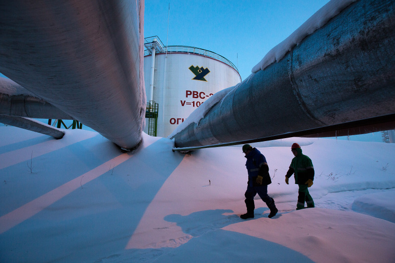 Employees pass beneath pipes leading to oil storage tanks at the central processing plant for oil and gas at the Salym Petroleum Development oil fields near the Bazhenov shale formation in Salym, Russia. Photographer: Andrey Rudakov/Bloomberg
