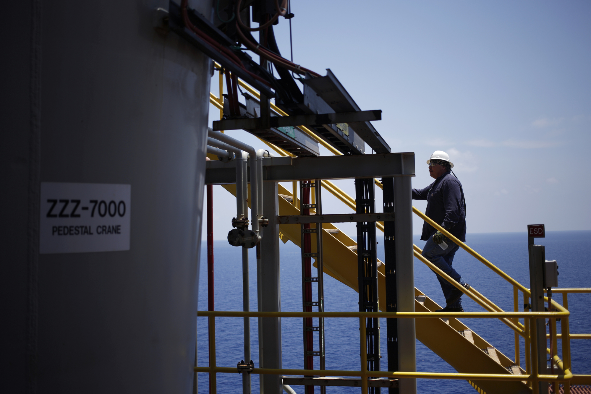 A offshore worker climbs a staircase aboard the Chevron Corp. Jack/St. Malo deepwater oil platform in the Gulf of Mexico off the coast of Louisiana, U.S., on Friday, May 18, 2018. While U.S. shale production has been dominating markets, a quiet revolution has been taking place offshore. The combination of new technology and smarter design will end much of the overspending that's made large troves of subsea oil barely profitable to produce, industry executives say. Photographer: Luke Sharrett/Bloomberg