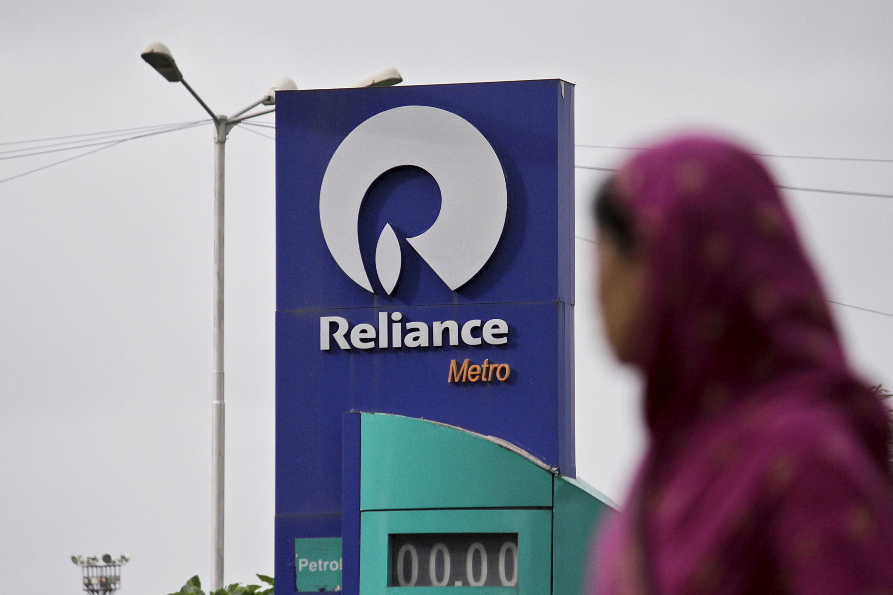 A woman walks past a Reliance Industries Ltd. gas station in Mumbai, India, on Thursday, July 19, 2012.  Photographer: Dhiraj Singh/Bloomberg
