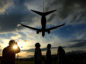People watch a Japan Airlines Corp. (JAL) aircraft approaching to land at the Osaka International Airport, operated by New Kansai International Airport Co., in Toyonaka City, Osaka, Japan. Photographer:Buddhika Weerasinghe/ Bloomberg