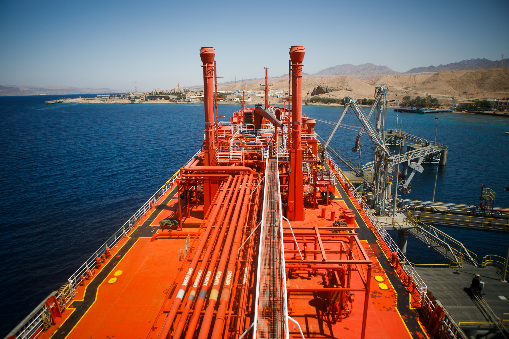 The 'Eugenia Gas' liquefied petroleum gas (LPG) tanker sits beside fuel transfer pipes at a terminal at Aqaba port, operated by Aqaba Development Corp., in Aqaba, Jordan, on Wednesday, April 11, 2018. Both the liquefied natural gas (LNG) and the LPG terminals were developed to secure the supply of gas resources after the disruption in Egyptian natural gas imports in 2010. Photographer: Annie Sakkab/Bloomberg