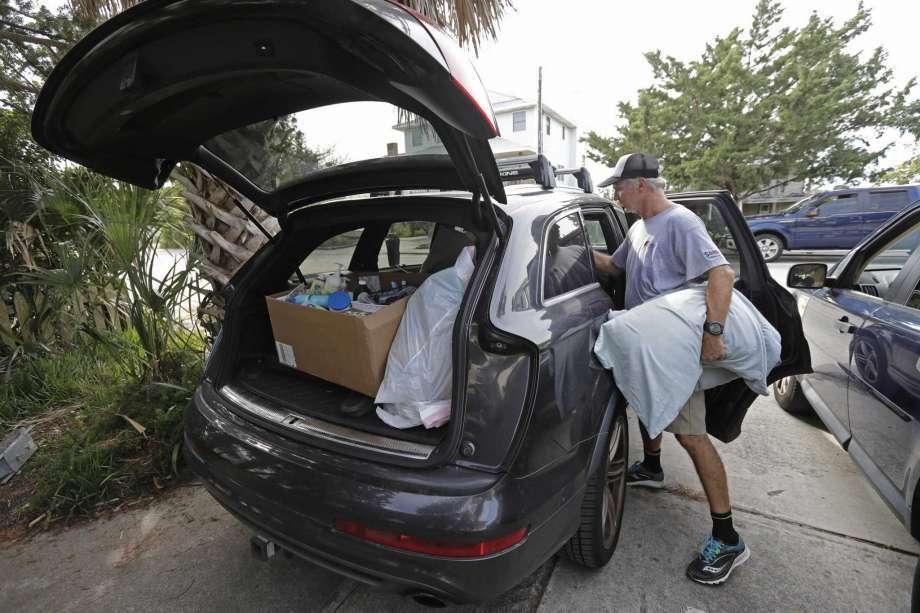 Jason Moore, of Raleigh, N.C., packs to evacuate from Wrightsville Beach, N.C., Wednesday, Sept. 12, 2018 as Hurricane Florence threatens the coast. (AP Photo/Chuck Burton)